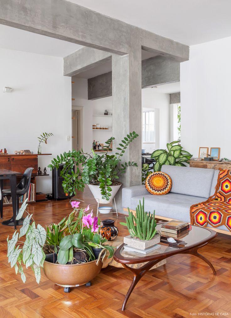 Sala de estar com piso de tacos e decoração que mistura móveis contemporâneos, vintage e muitas plantas.