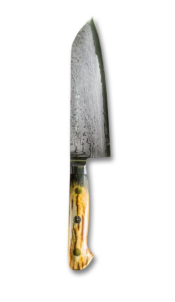 Couteau de cuisine Santoku  La lame de ce couteau de chef est faite de 69 couches imbriquées d'acier inoxydable dur et mou. Utilisée pour les sabres traditionnels japonais, cette technique de forge fait que cette lame est incroyablement difficile à briser ou à plier, lui donnant une durabilité à vie ! Les traces de carbones forment le motif de volutes similaires au grain naturel du bois.