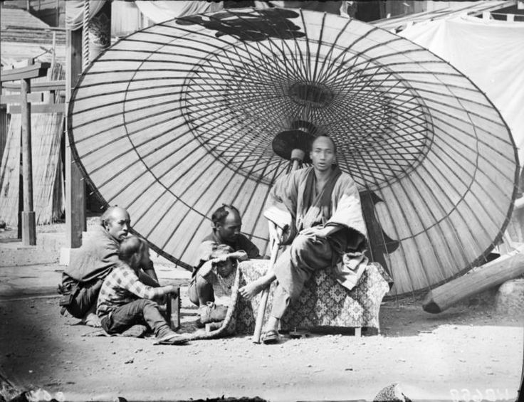 A yakonin with his servants under an enormous umbrella. Yokohama, ca. 1869-1870 by Wilhelm J. Burger