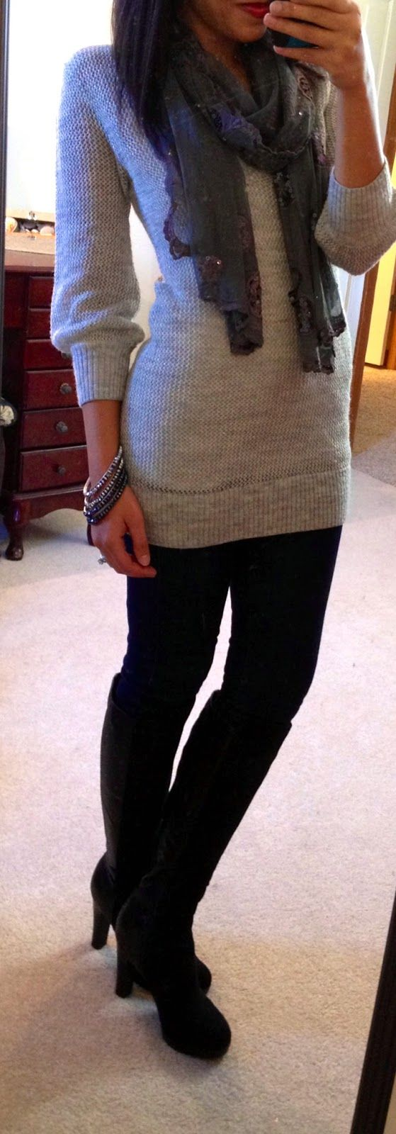 Grey tunic with black leggings and black boots.