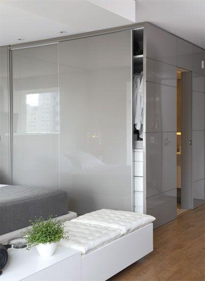 """Para disfarçar o volume do banheiro, Toninho Noronha revestiu a entrada do ambiente com um lambri de madeira de laca PU cinza-brilhante. """"O mesmo acabamento foi dado às portas do armário, criando um bloco único"""