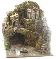 Paesaggio per presepe altezza cm 40 con grotta e case arroccate sulla roccia comunicanti tramite scalinata, luce con presa 220 volt. Realizzato in modo artigianale, a mano usando legno, sughero, gesso, cortecce d''albero, ramie muschio. Artigianato napoletano. Base 35X37 cm.