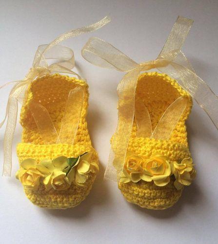 Patucos sandaliaspara bebe tejidas en ganchillo crochet en amarillo con florecitas en mismo tono y lazos de organza en el mismo color para ajuste al pie. www.lafabricadecucadas.com