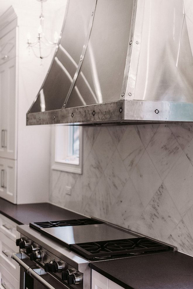 Grey tones from the island reflected here in the diagonal marble tile backsplash and the stunning stainless hood. Interior Design Ideas