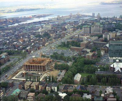 Vue aérienne de la colline parlementaire en 1968. On aperçoit, au premier plan, le Grand Théâtre alors en construction. On distingue également plusieurs espaces de stationnement aux abords du boulevard Saint-Cyrille. Ceux-ci feront place au parc de l'Amérique-française en 1979 et à l'édifice Hector-Fabre en dix ans plus tard. (Vue aérienne de la construction du Grand Théâtre à Québec, Neuville Bazin - 1968, BAnQ, Fonds Ministère de la Culture et des Communications, E6,S7,SS1,P6810944).