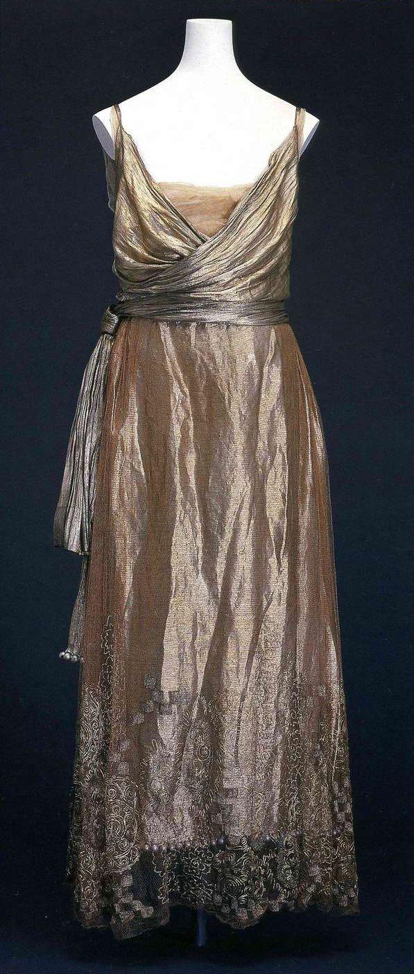 Вечернее платье. Поль Пуаре, около 1920. Серебряная ткань ламе, шелковый тюль на груди, верхняя юбка из шелкового тюля с серебряной вышивкой, растительный и геометрический узоры, пояс из такой же ткани, деревянные бусины.