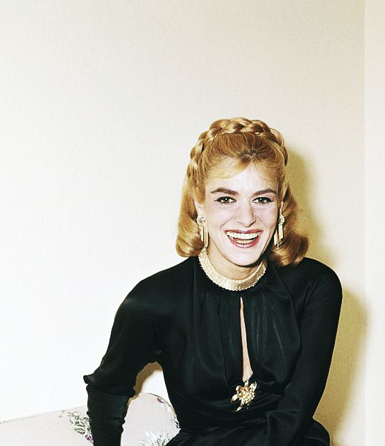 Melina Mercouri pictured seated on a chair wearing a black evening dress with gold jewellery in London in 1962. Via http://hollywoodlady.tumblr.com/