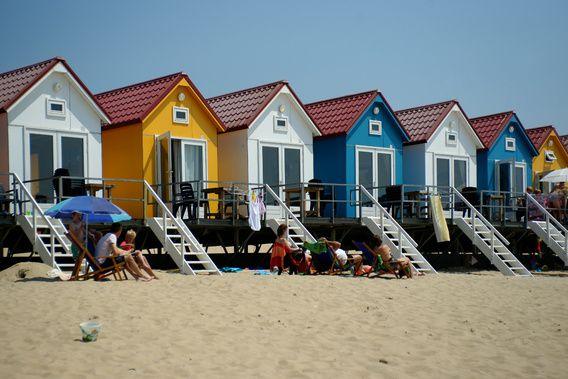 Strandhuisjes in Vlissingen. Het Nollenstrand op een warme zonnige dag. Kleurrijke strandhuisjes in wit, geel, turquoise, rood en blauw.