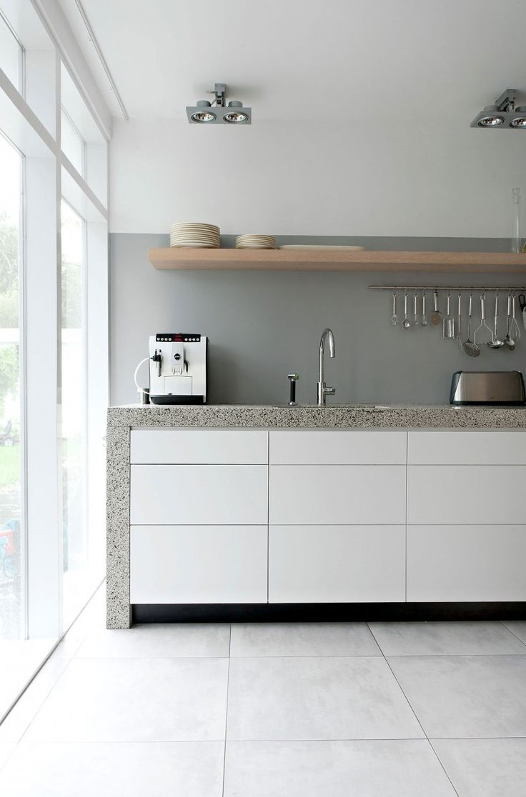 A simple white contemporary kitchen | Porcelain floor tiles like this can be sourced from Mandarin Stone