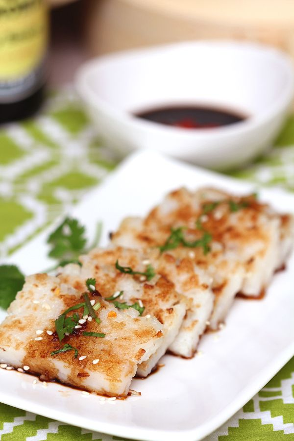 Turnip Cake (Lo Bak Gou) - Loaded with shredded  turnip, steamed and pan fried until crispy golden brown. Garnished with fresh cilantro and served with soy sauce and chilli. A delicious savory delight!