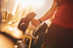 Unrecognizable person taking dumbbells in a gym. stock photo