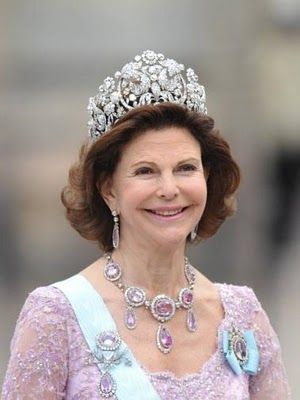 Queen Silvia, mother of the bride wore the Braganca diamond tiara that once belonged to Empress Amalie of Brazil. We found her pink Topaz necklace and earrings set especially eye-catching, and tastefully coordinated with her pastel pink gown.