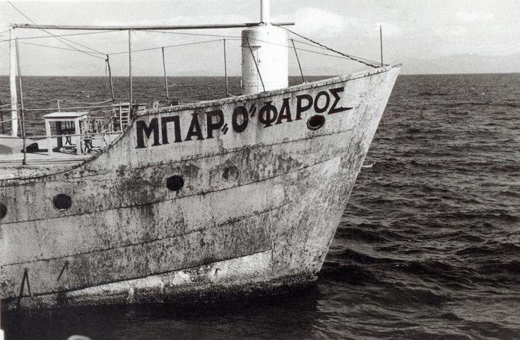 """Η ιστορική φωτογραφία του Ανδρέα Εμπειρίκου που τραβήχτηκε τον Οκτώβριο του 1953. Το Bar Ο Φάρος του Ασημάκη Καλπάκη Στο καμπούνι της πλώρης του τσιμεντόπλοιου της Ραφήνας.  Απίστευτες ιστορίες της καθημερινότητας εκτυλίχθηκαν εδώ. Βιώματα και μνήμες. Μια ζωντανή ιστορία που δεν πρέπει να σβήσει.  Η φωτογραφία περιλαμβάνεται στο λεύκωμα [b]""""Η Άνδρος του Ανδρέα Εμπειρίκου"""",[/b] το οποίο εκδόθηκε από τις εκδόσεις [b] """"Άγρα""""[/b] και την ..."""