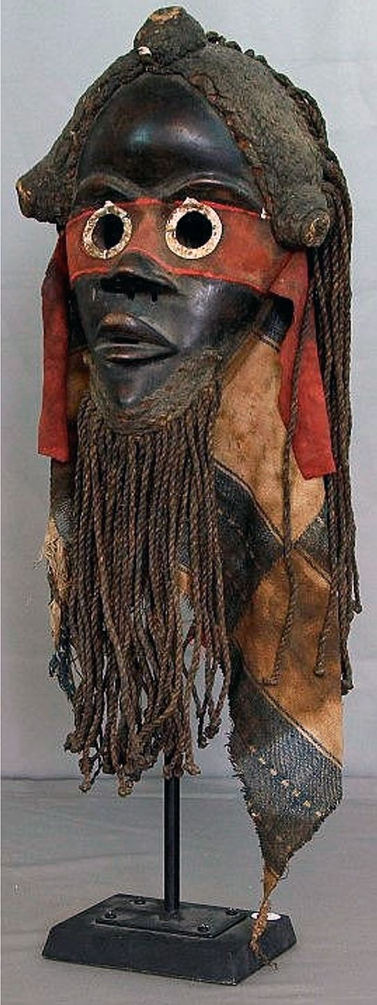 Africa   Zakpai mask from the Dan people   Wooden face with round pierced eyes with metal rings over a red fabric around eyes, protruding pierced lips and attachment of braided coiffure and beard.      Zakpai masks are used to enforce fire prevention. The wearer monitors bonfires and punishes those whose bad practices endangers the village