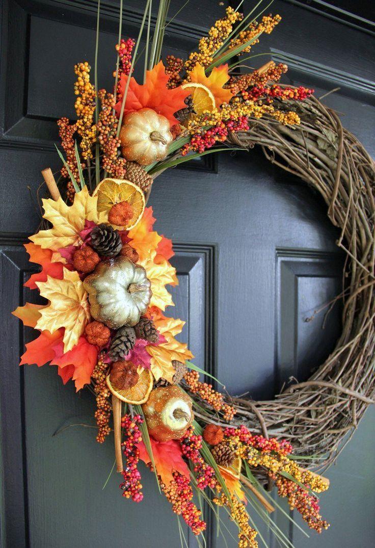 couronne d'automne artisanale composée de brindilles, potirons décoratifs, citrouilles et baies rouges