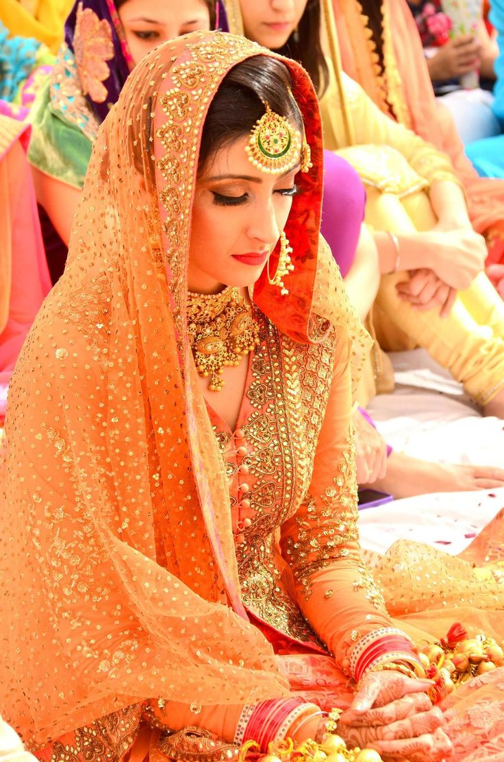 Love this entire look- the coral/orange Sabyasachi outfit, the gold necklace, that teeka and the make up. Perfect!