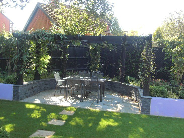 Small, shallow, contemporary garden design in Bracknell, Berkshire with raised borders, rendered blockwork walls, chunky pergola over secluded seating area. Designed by Linsey Evans Garden Design www.linseysgardens.com