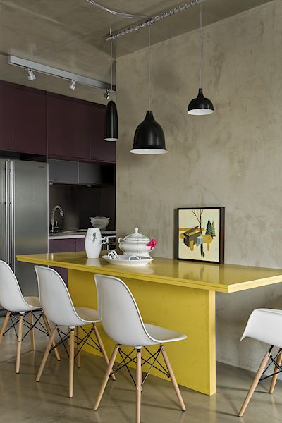 Žlutá barva jídelního stolu je zajímavým zpestřením nastavené barevné palety interiéru.