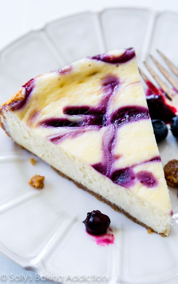 Ultra creamy Blueberry Swirl Cheesecake on a buttery, thick graham cracker crust. Guests will be begging for seconds! @sallybakeblog