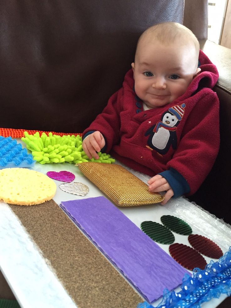 Riley with his sensory board that Nana made for him