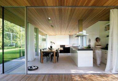 Die weiße Wohnküche in einem Haus am Bodensee überzeugt mit ihrer Offenheit. Dank der großen Glastüren geht sie fast schwellenlos auf die Terrasse über und erweitert an schönen Tagen den Wohnraum nach draußen. Ihre weißen Küchenfronten setzen einen frischen Kontrast zu den natürlichen Bau-Materialien wie Kalkstein am Boden und Zedernholz an der Decke.