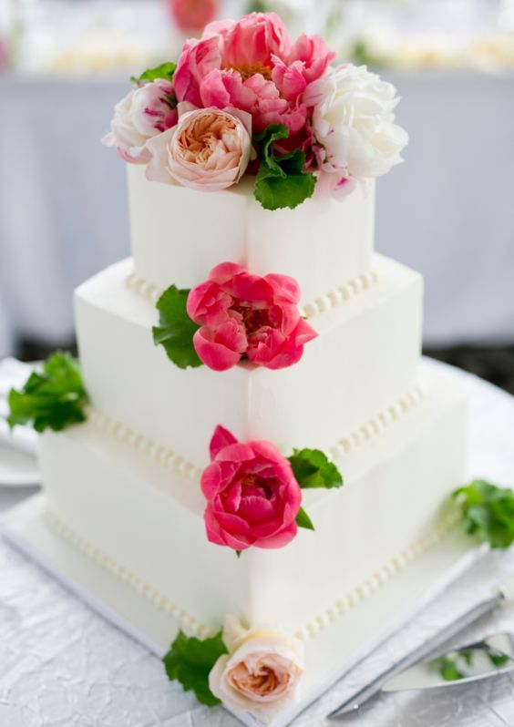 Charming three tier square white wedding cake accented with bright pink flowers; Featured Cake: Alliance Bakery