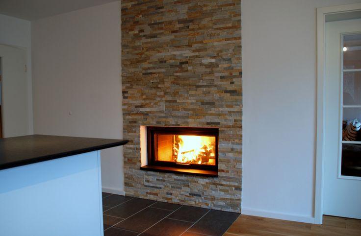 Heizkamin mit einer Wandverkleidung aus Naturstein. #Naturstein #Fireplace #OfenModern www.ofenkunst.de