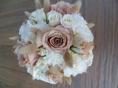 quicksand roses, chablis spray roses, white carnations, white tulips, white sola wood flowers, seeded eucalyptus, cypress, douglas fir, camellia buds, holly, sponge mushrooms, wheat, sweet gum balls, white hypericum, star of bethlehem, yoko ono, or kermit mums by Urban Poppy