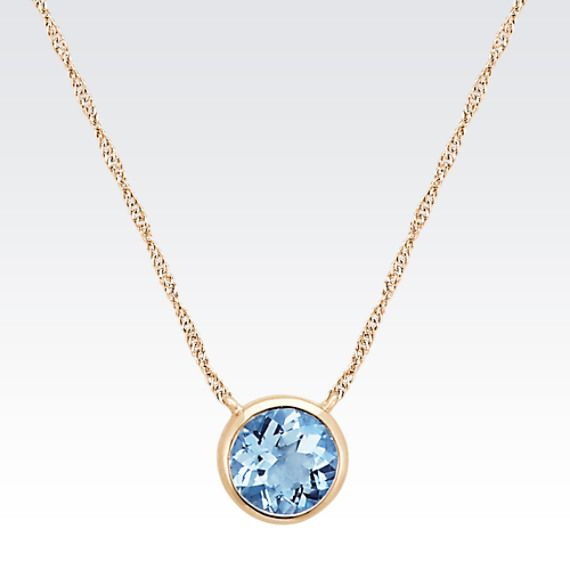 This classic and elegance necklace is part of our Studio collection and displays one round blue aquamarine, at approximately 1.23 carats. The gemstone is held in a bezel setting crafted of quality 14 karat yellow gold and hangs from a matching 18-inch Singapore chain secured by a spring ring clasp. This necklace measures 1/4 inch in diameter across the solitaire gemstone.