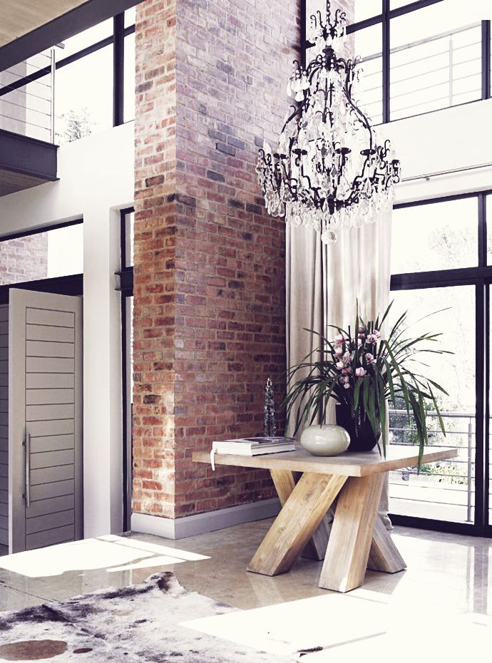 big entry table + chandelier + exposed brick