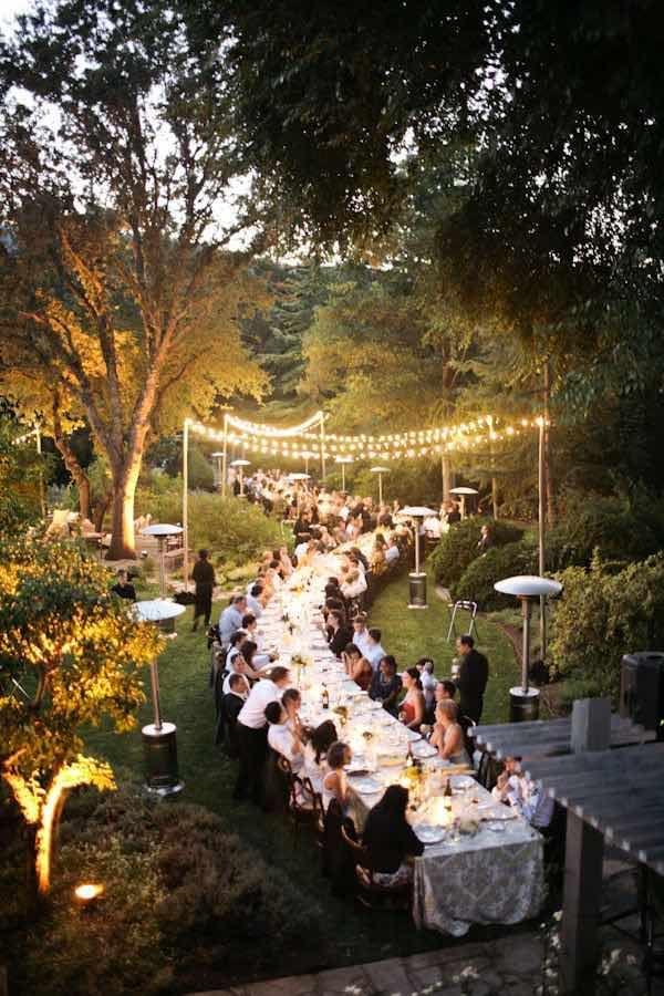 Una interminable mesa en un jardín iluminado con luces colgantes y drapeadas luces navideñas en los árboles y arbustos que la rodean. En suma, una elegante boda de noche de verano.