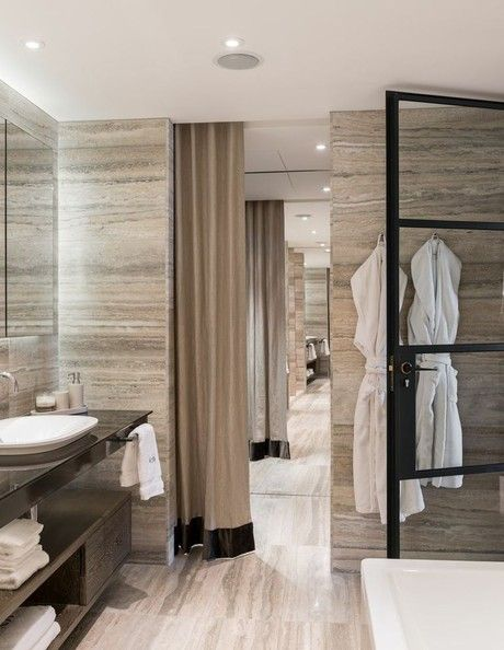 Tara Bernerd's London Apartment / Wall-to-wall travertine makes a hotel-worthy moment in Bernerd's ultra-luxe bathroom.   House of Eroju's Moscow Lever Handles used on the bathroom doors.