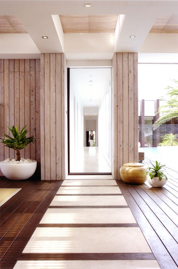 Stone inlays in the wood floor provide interest and a durable pathway to the hallway beyond...