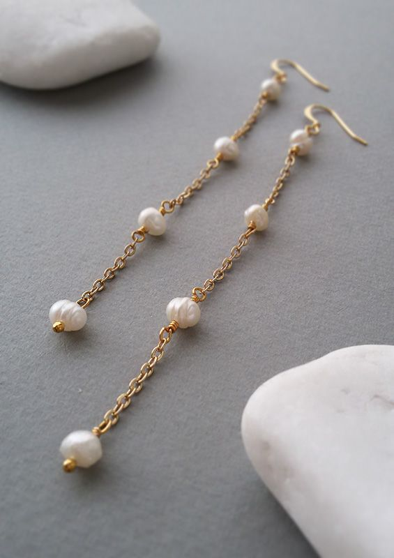 Gold plated long dangle earrings with freshwater pearls.