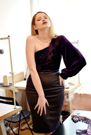 VAL is a purple velvet dress. The dress has a tight fit and a tight, dark purple waistband. The top part is made from a darker cyclamen velvet with an asymmetric neckline and a voluminous sleeve. The bottom part is made from a stiffer type of dark purple velvet. Lace attachments on the top and bottom part.