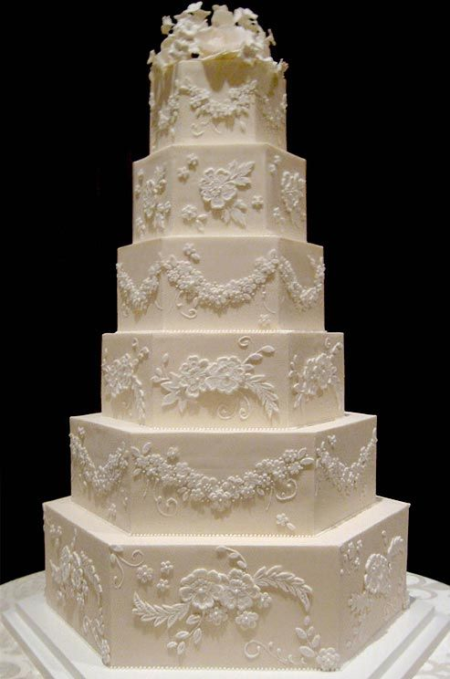 This six-tiered hexagonal cake is decorated with intricate floral details and topped with sugar flowers.