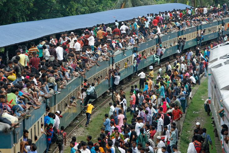 People attempt to climb aboard an overcrowded train at a railway station in Dhaka, Bangladesh. Millions of residents are traveling home from the capital city to celebrate the Muslim Eid al-Fitr holiday, which marks the end of the holy fasting month of Ramadan.