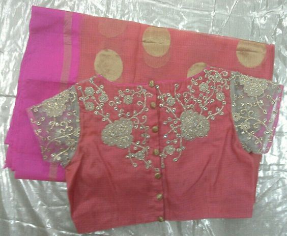 Peach Kota saree with pink border paired with boat neck blouse at front and back open at the back with zari embroidery.