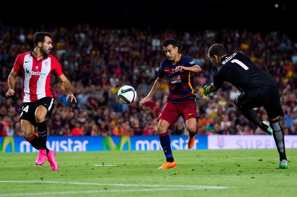 Pedro Rodriguez (C) of FC Barcelona kicks the ball between Mikel Balenziaga (L) and Gorka Iraizoz of Athletic Club during the Spanish Super Cup second leg match between FC Barcelona and Athletic Club at Camp Nou on August 17, 2015 in Barcelona, Catalonia.