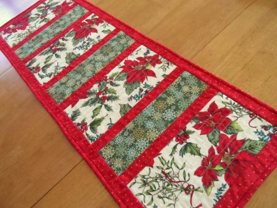 Christmas table runner in red, green and ivory. This modern holiday table runner is a delight to look at and features a poinsettia and holly focal fabric and a snowflakes fabric as a secondary focal fabric. This handmade quilted contemporary table runner can be used on your dining room table, buffet table, or coffee table.  All fabrics used are 100% cotton quilting holiday fabrics. The red border fabric has small gold metallic dots. The backing used is the poinsettia focal fabric. A layer of…