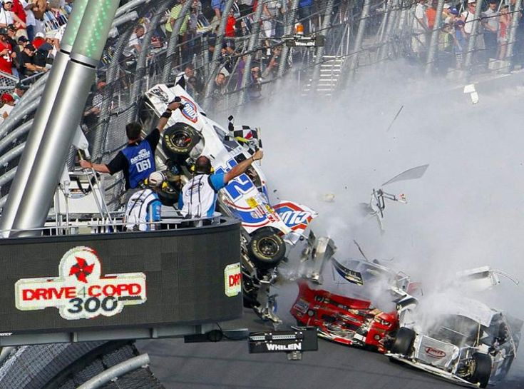 Daytona Beach, FL 2-23-2013   View From The Flag   NASCAR race officials and a photographer get a bird's-eye view of the unfolding spectacle at the END of 2013's first Nationwide Series race. (David Graham/AP)   At least 12 cars were swept into a melee on the final lap, with rookie Kyle Larson's car lifting off the ground and slamming wheels-first into the front stretch grandstands near the flag stand. The front wheels and engine from Larson's car flew into the grandstands.