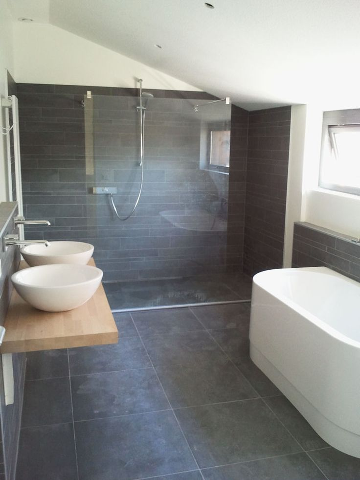 Dark tiles with wooden vanity and white sinks etc