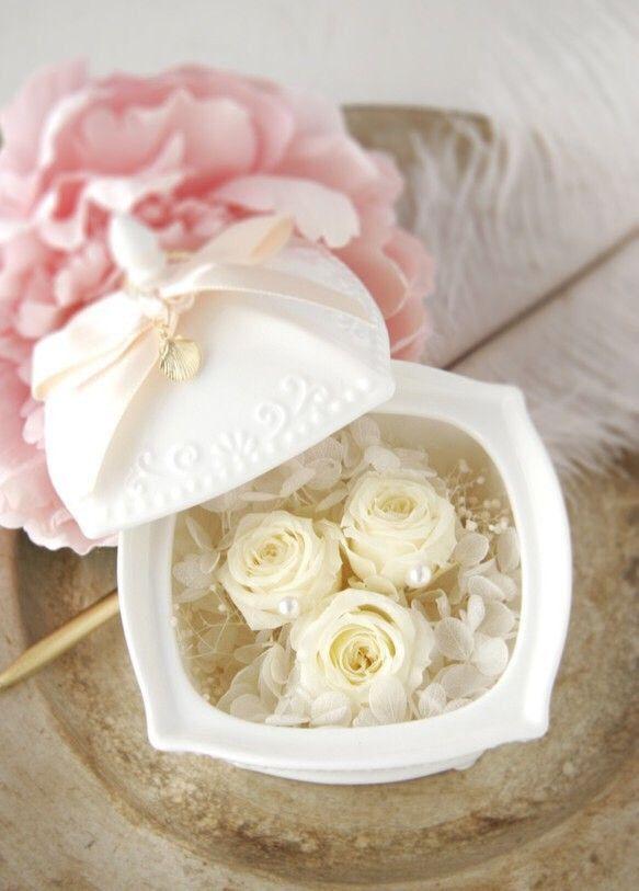 """結婚指輪を置いておくリングピロー。Chere(シェール)は、""""いとしい…""""を表します。アンティーク調の白い陶器の蓋には、ゴールドの鍵のチャームとリボンをプラス。チャームは2種類(鍵/貝殻)より、リボンのお色は(ピンク/ミントグリーン)の2色よりお選びいただけます。とても上品で可愛らしいデザインです。蓋をあけると白いローズとアジサイのプリザーブドフラワーを敷き詰められています。パールの部分に結婚指輪を置いて、ご使用下さい。結婚式後もジュエリーケースとして飾っておけますね^^**オリジナルギフトBOXに入れてお届け致します**おしゃれなギフトBOXなので、結婚お祝いのプレゼントにもピッタリです。(BOX画像の中身はサンプルです)ーーーーーーーーーーーーーーーーーーーーーーーーーーーーーーーー①チャームを《鍵》と《貝殻》のどちらかお選びください。②リボンのお色を《ピンク》または《ミントグリーン》のどちらかお選びください。以上2点を備考欄にご記入下さい。ーーーーーーーーーーーーーーーーーーーーーーーーーーーーーーーー素 材 ::: 陶器・プリザーブドフラワーcolor…"""