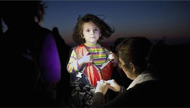Η φωτογραφία της χρονιάς του έλληνα φωτογράφου Αγγελου Τζωρτζίνη. Ενα κοριτσάκι που μόλις έφτασε με ένα καϊκι στην Κω δέχεται τη βοήθεια μιας διασώστριας που της αφαιρεί το σωσίβιο.