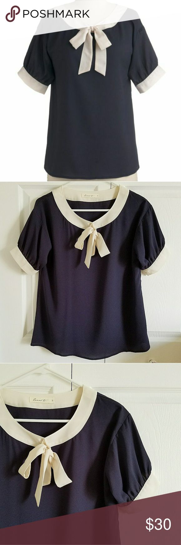 MOD CLOTH Blue Madeline Blouse Sweet Bow COMME TOI Women's COMME TOI Modern Madeline blouse. Size Small. Loose fitting. Dark blue in color with soft white details. Neck ties into a bow. Short sleeves. 100% polyester. Purchased from MOD CLOTH.  Measurements (while lying flat): Shoulder to shoulder- 18 inches Armpit to armpit- 29 inches Sleeve length- 7 1/2 inches Top to bottom hem- 24 inches  PREOWNED. Never worn. No rips, stains or odor.  *First photo is a stock photo. Comme Toi…
