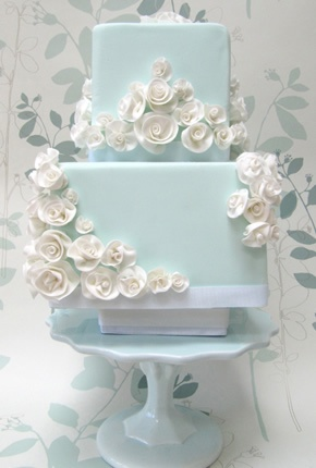 Delicioso pastel azul con decorado en flores blancas.
