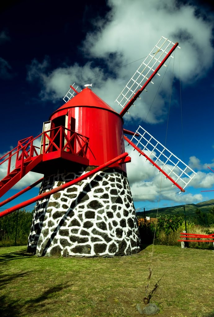 "Windmill in Faial, Azores  How many of these did I see growing up?  I think we even had a toy-like replica at one point.  I love wind, especially listening to it move through the trees, like whispers to my soul.  This windmill with its ""wholey"" blades reminds me of our vulnerabilities.  We aren't solid form, energy passes through us but the whispers on the wind can still move us to extraordinary heights.  It reminds me to live on purpose!"
