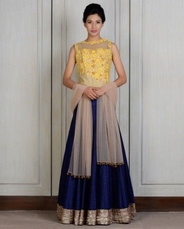 Yellow Blue Corset Lengha Corset: Beige raw silk panelled corset with yellow resham and sequin embroidery on the front and sheer net back. Side Zip Skirt: Blue raw silk skirt with hand-sewn sequins embroidered border and drawstring waist. Dupatta: Beige net dupatta with velvet golus.