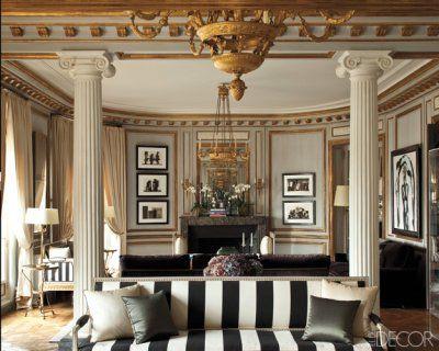 The living room of a Paris apartment decorated by Frédéric Méchiche: black and white stripes, white pillars, gilt detailing.  Via Elle Decor...