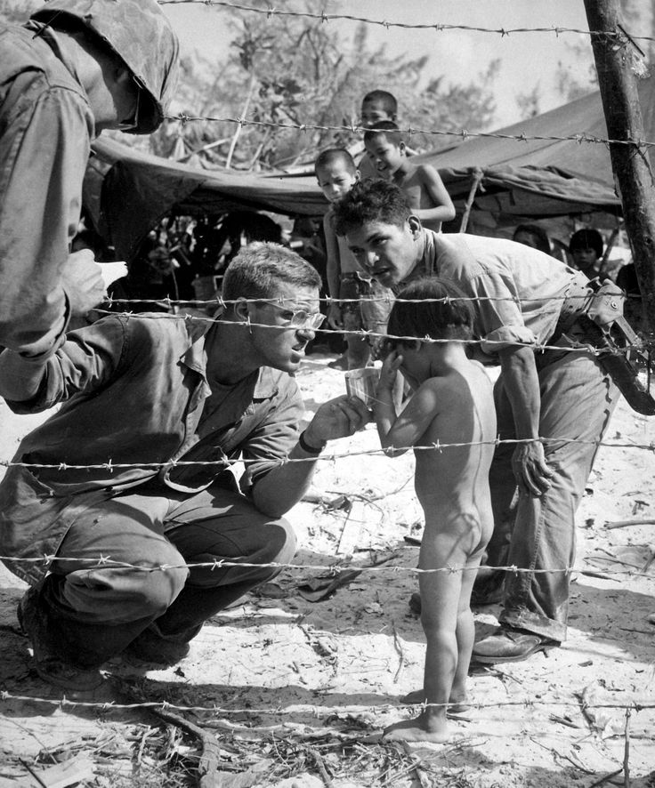 U.S. Marines try to soothe a crying child by offering a shiny rations tin. Island natives are sheltered with their families in a camp set up for refugees from battle areas by U.S. Marine Civil Affairs authorities during the Battle of Saipan. Saipan, Northern Mariana Islands. July 1944.  Image taken by U.S. Coast Guardsman Ted Needham.